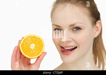 Woman holding an orange while placing her tongue on her lips - Stock Photo