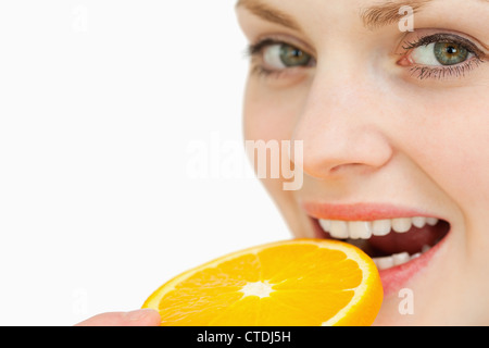 Close up of a woman placing a slice of an orange in her mouth - Stock Photo