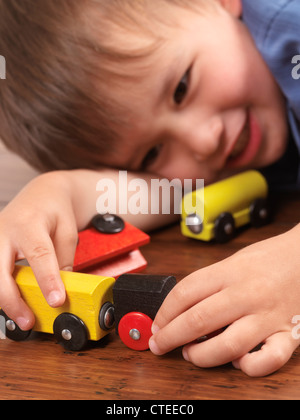 Happy two year old boy playing with a colorful toy train on hardwood floor - Stockfoto