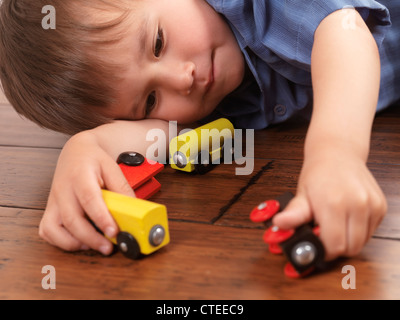 Two year old boy playing with a colorful wooden toy train on hardwood floor - Stockfoto
