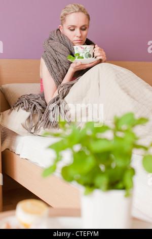 Sick woman drinking herbal tea - Stock Photo