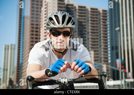 USA, California, Los Angeles, Portrait of young man road cycling on city street - Stock Photo