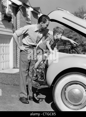 1940s FATHER & SON CHECKING UNDER HOOD OF CAR IN DRIVEWAY - Stock Photo