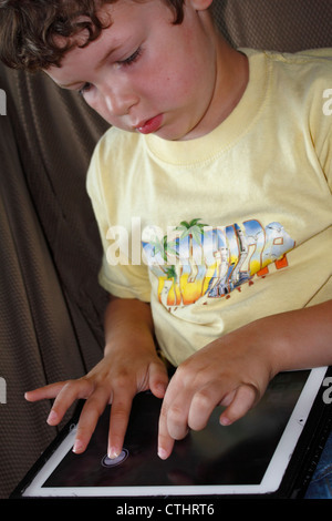 A 5 or 6 year old Caucasian boy using an iPad tablet computer wireless electronic internet device - Stock Photo