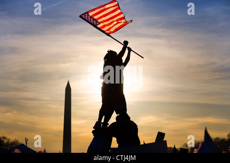 Two immigrants on top of human pyramid waving a U.S. flag in Iwo Jima fashion at march of illegal immigrants in - Stock Photo