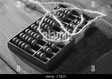 An antique wooden abacus. on a wooden bench, Black and White Photograph - Stock Photo