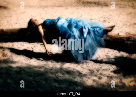 a woman in evening dress lying on a tree trunk - Stock Photo