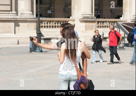 Paris, France - Young tourist couple taking photo of themselves - Stock Photo