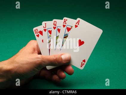 A man's hand holding playing cards on a green table.A Royal Flush in hearts in the game of Poker - Stock Photo
