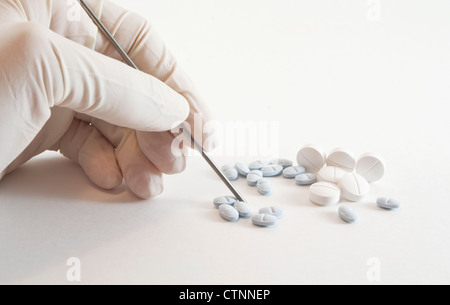White latex gloved hand holding, counting and preparing medicinal prescription blue and white pills isolated on - Stock Photo