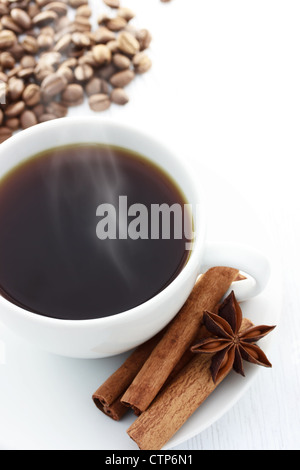 Cup of Hot Coffee with Cinnamon Sticks, Star Anise and Coffee Beans on a white table - Stock Photo