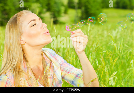Pretty woman blowing soap bubbles in park, healthy beautiful female playing on green grass, carefree model relaxing - Stock Photo