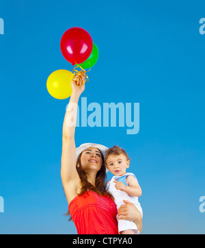 Happy family holding colorful air balloons over blue sky background, mother and adorable child baby boy playing - Stock Photo