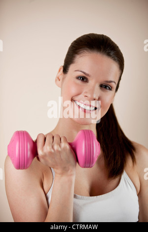 A young woman holding a pink dumbbell, smiling to camera - Stock Photo