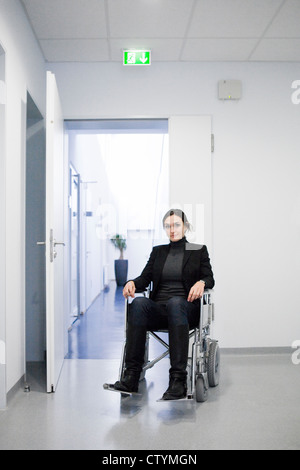 Young disabled woman on wheelchair in hospital environment - Stock Photo