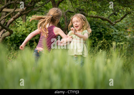 Girls running together in tall grass - Stockfoto