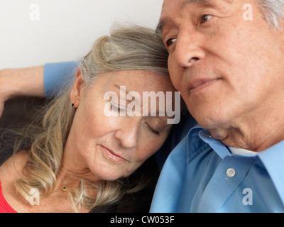 Older woman napping on husband - Stock Photo