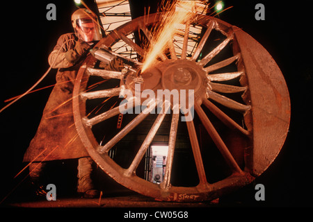 A fettler works on the 6ft 8 inch Driving wheels of LNER Class A1 Steam Locomotive 60163 Tornado at a foundry in - Stock Photo