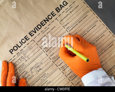 Scientist filling out evidence bag - Stock Photo