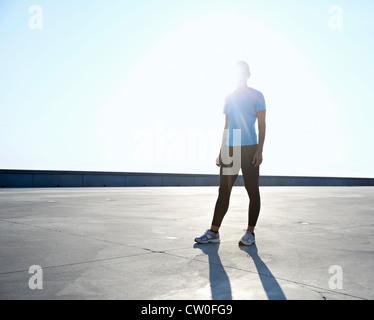 Runner standing on rooftop - Stock Photo