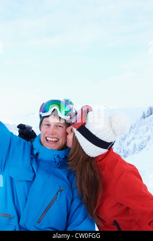 Skiers kissing in snow - Stock Photo