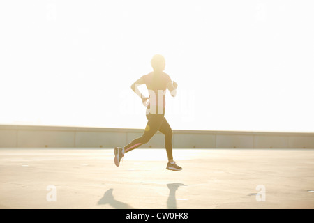 Man running on rooftop - Stock Photo