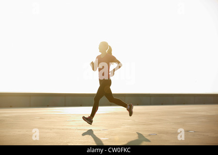 Woman running on rooftop - Stock Photo