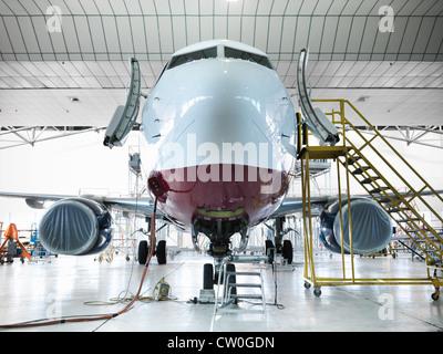Airplane docked in hangar - Stock Photo