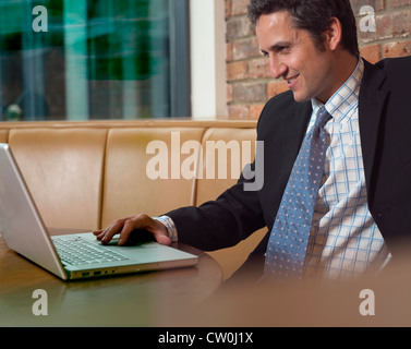 Businessman working on laptop in cafe - Stockfoto