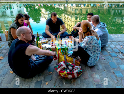 Paris, France, Group Young French People Picnicking in the 'Canal Saint Martin' Area, Sharing Drinks in Evening - Stock Photo