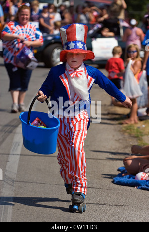 Boy Dressed as Uncle Sam Carrying Candy in Blue Bucket to Hand Out to Children along Parade Route in New Pekin, - Stock Photo