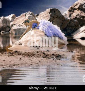 a woman in evening dress lying on a rock in the water - Stock Photo