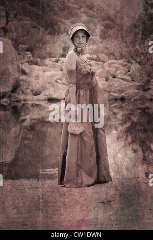 a young woman in a period dress standing on the shore of a lake - Stock Photo