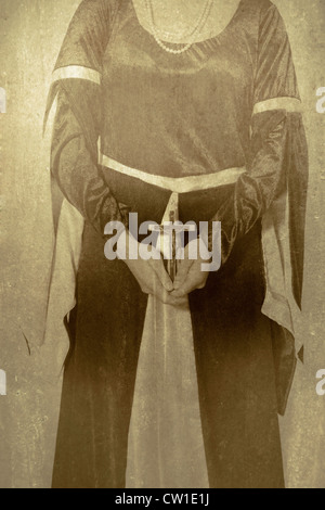 a woman in Victorian dress holding a crucifix in her hands - Stock Photo