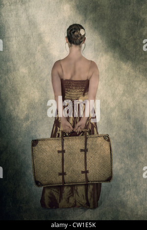 a woman in a period dress holding a small, old suitcase behind her back - Stock Photo
