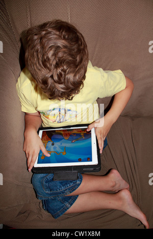 A six year old boy using an iPad tablet computer and playing a game on it while sitting on a sofa - Stock Photo
