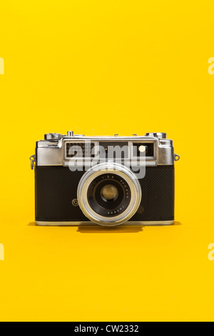 Retro analog film camera on yellow background - Stock Photo