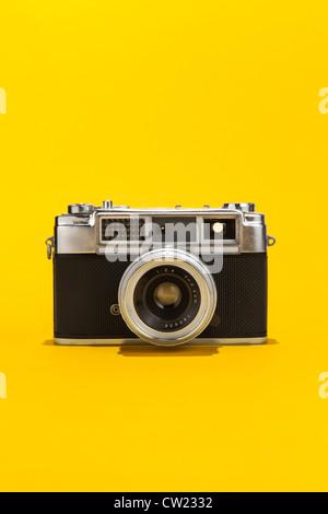 Retro analog film camera on yellow background - Stock Photo