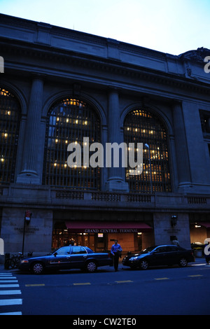 Dawn portrait arched windows, blue shirt man between 2 cars parked entrance Grand Central Terminal, Vanderbilt Avenue, - Stock Photo