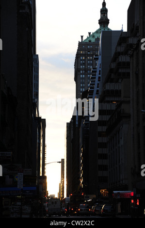 Urban alley portrait , towards Helmsley Building, red lights traffic moving towards dawn sunrise, West 46th Street, - Stock Photo