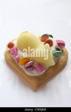 sugar mouse on heart shaped biscuit with dolly mixtures isolated on white background - Stock Photo
