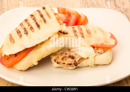 Toasted Chicken, tomato and mozzarella Panini sandwich that has been cut in half and placed on a plate - studio - Stockfoto