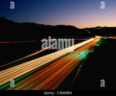 Highway with light streaks from vehicles at dusk - Stock Photo