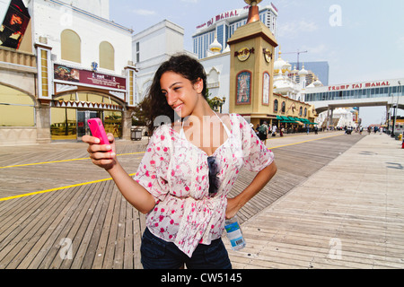 USA, New Jersey, Atlantic City, Boardwalk, Woman Checking Messages on Smartphone - Stock Photo