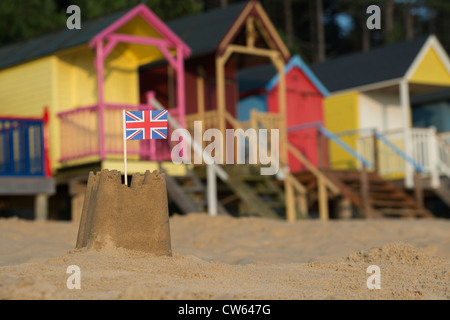 Union Jack flag in a sandcastle in front of colourful beach huts. Wells next the sea. Norfolk, England - Stock Photo
