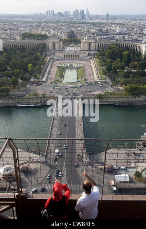 Tourists point out landmarks from the second level of the Eiffel Tower, Paris. - Stock Photo