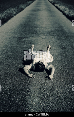 a woman in a white dress lying on a street - Stock Photo