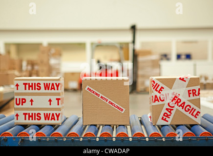 Three cardboard boxes with parcel tape on conveyor belt - Stock Photo