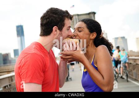 Couple eating hot dog on Brooklyn Bridge - Stock Photo