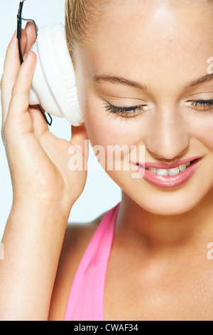 Young woman listening to music on headphones - Stock Photo